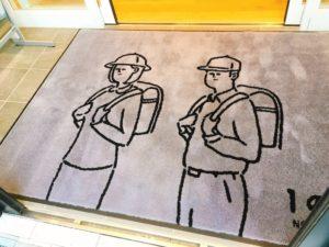 玄関マットにはランドセルを背負った大人のイラストが書かれています